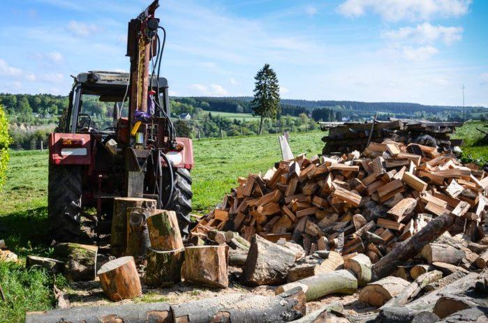 old-tractor-with-hydraulic-powered-log-splitter-and-pile-of-firewood