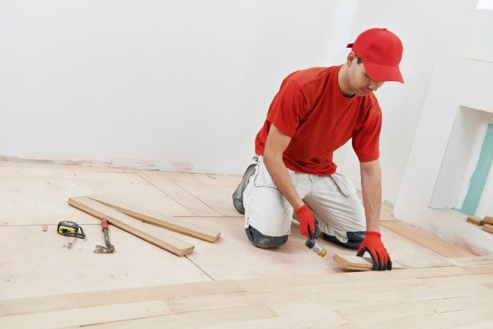 carpenter worker installing wood parquet board during flooring w