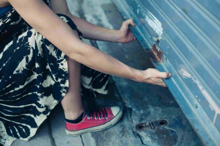 A woman is unlocking and opening a garage door