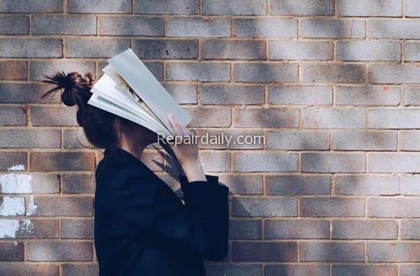 student hiding her face with book