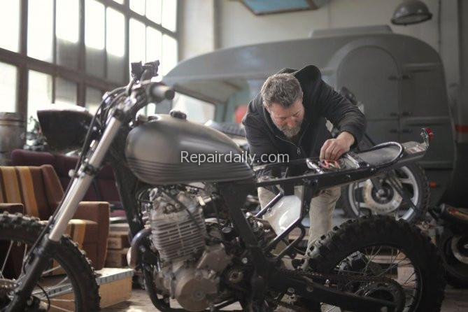 man repairing motorcycle bike