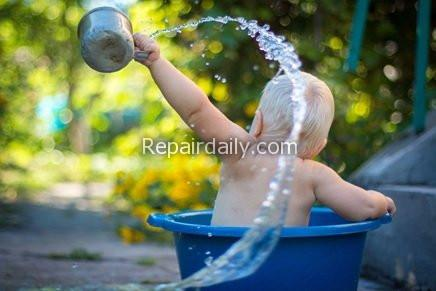 child playing on bucket water